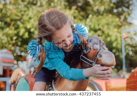 Kid girl riding on a toy horse at park - stock photo