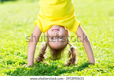 kid girl standing upside down on her head on grass in summer - stock photo