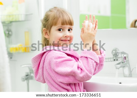 kid girl washing her hands in bathroom - stock photo