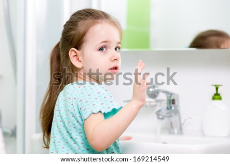 kid girl washing his face and hands in bathroom - stock photo