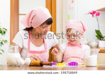 kid girl with her mother cooking in the kitchen - stock photo