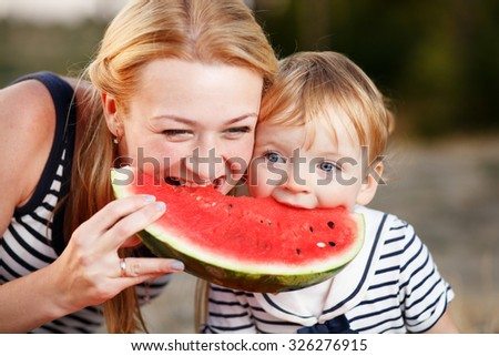 Kid girl with mom at countryside eating watermelon. - stock photo