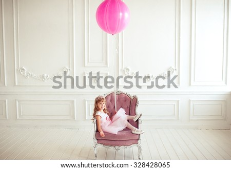 Kid girl 4-5 year old sitting in armchair holding pink balloon in room over white background. Looking at camera. Childhood. Cute little princess.  - stock photo