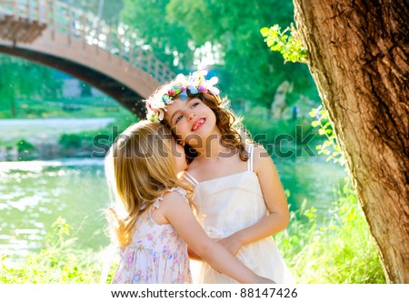 kid girls playing in spring outdoor river park whispering ear - stock photo