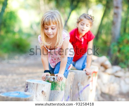 kid girls playing on trunks knee walking in forest nature - stock photo