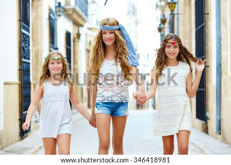 Kid girls walking hand in hand at white Mediterranean village of Spain - stock photo