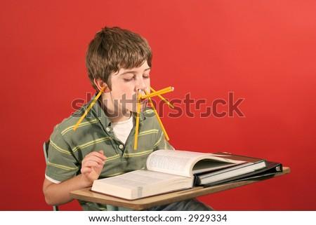 kid goofying off while studying - stock photo