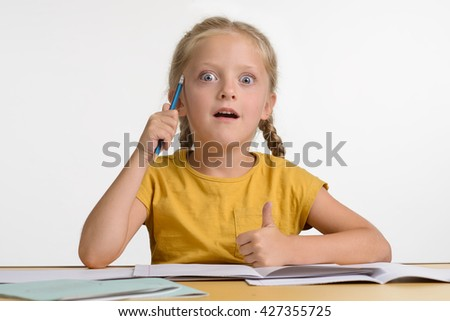 Kid got too much information so she is enormously amazed. Opened big blue eyes and mouth. Child holds a pencil in her hand.  - stock photo