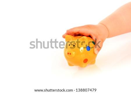 Kid hand and piggybank over white. - stock photo