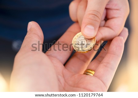 kid hand giving one pound coin stock photo royalty free 1120179764
