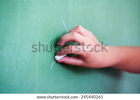Kid hand holding a white chalk about to write or draw on empty green chalkboard. - stock photo