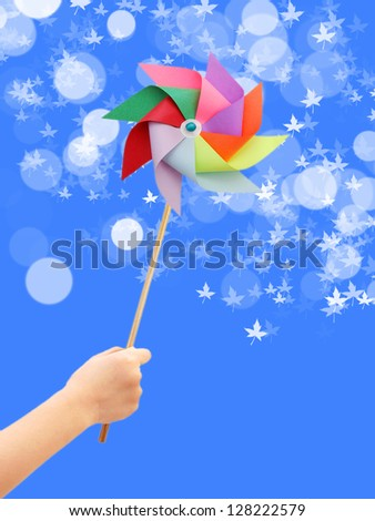 Kid hand holding colorful pinwheel close up isolated on white background. - stock photo