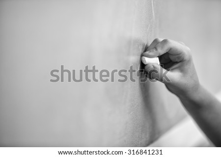 Kid hand writing on chalkboard. - stock photo