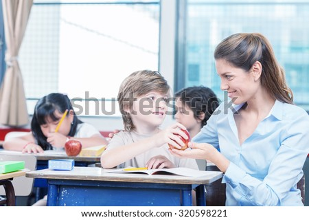 Kid handing red apple to teacher in elementary school. - stock photo
