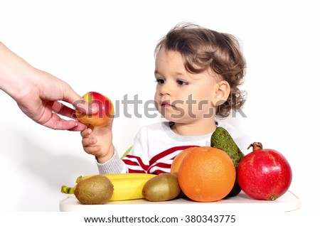 Kid having a table full of organic food. Cheerful toddler eating healthy salad and fruits. Baby choosing between apples, bananas, oranges, avocado,pomegranate. kiwi. Isolated on white - stock photo