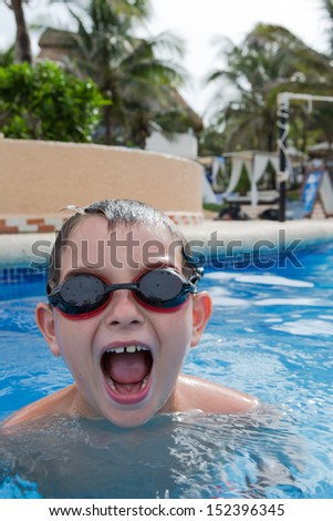 Kid having blasting fun in the swimming pool with his goggles on - stock photo