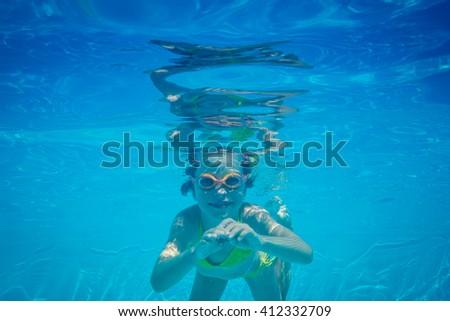 Kid having fun in swimming pool. Underwater portrait of child. Summer vacation - stock photo