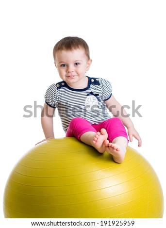 Kid having fun with  gymnastic ball isolated - stock photo