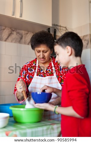 Kid helping his grandmother making cookies in the kitchen