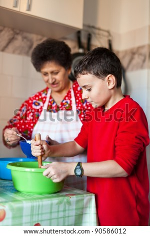 Kid helping his grandmother making cookies in the kitchen - stock photo