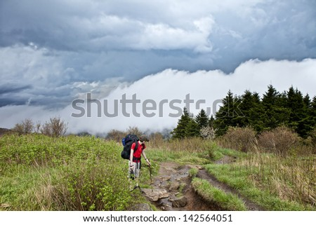 kid hiking with approaching storm - stock photo