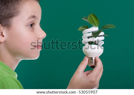 Kid holding a compact fluorescent bulb with a leaf. Global wamring concept. On green backdrop