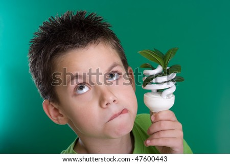Kid holding a compact fluorescent bulb with a leaf. Global warming concept. On green backdrop - stock photo