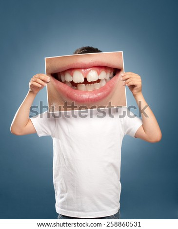 kid holding a picture of a mouth smiling - stock photo