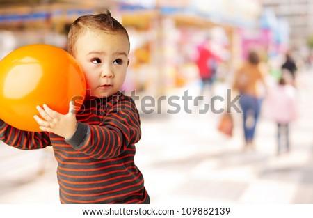 kid holding an orange balloon at a mall - stock photo