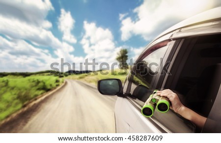 kid holding binoculars out of the car window on the road trip