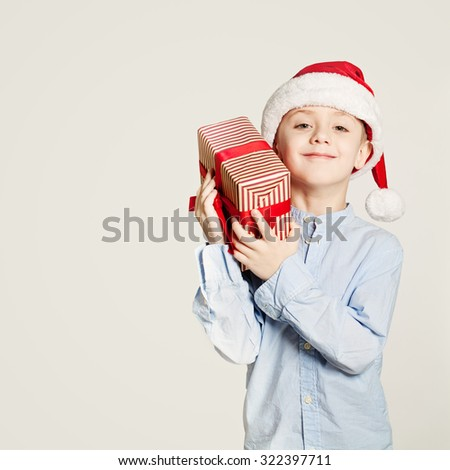 Kid holding Christmas Gift Box. Child Boy and Gift on Background with Copy Space  - stock photo
