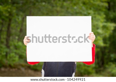Kid holding empty paper in hands - stock photo