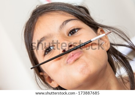 Kid holding paintbrush between nose and mouth - stock photo