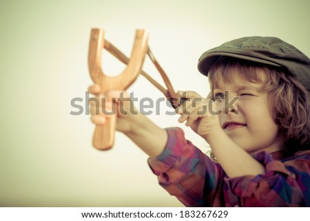 Kid holding slingshot in hands against summer sky background. Retro style - stock photo