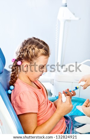 Kid holding toothbrush and toothpaste in hands