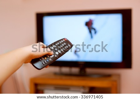 Kid holding TV remote controller  - stock photo