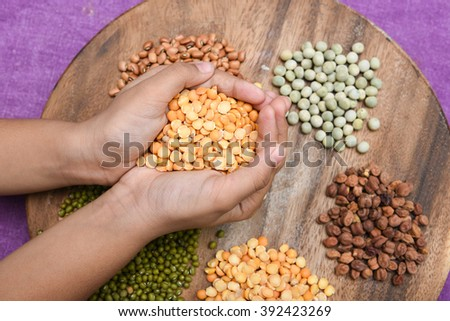 Kid holding yellow Lentils/ bean/ dhal in hand with pulses of various colors on wooden circle shape base/ split peas, top view Kerala, India. legumes chickpeas, green mung, rice and dal - stock photo