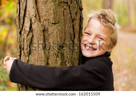 kid in a forest hugging a tree - stock photo