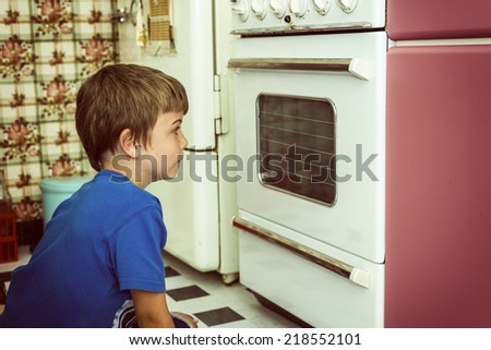 kid in a vintage kitchen looking if the cookies are ready,vintage filter added - stock photo