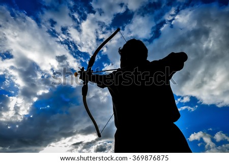 Kid in actions practice with archery during evening in silhouette