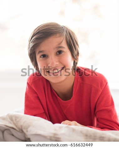 Kid in bedroom sleepin on bed with white sheet and pillow