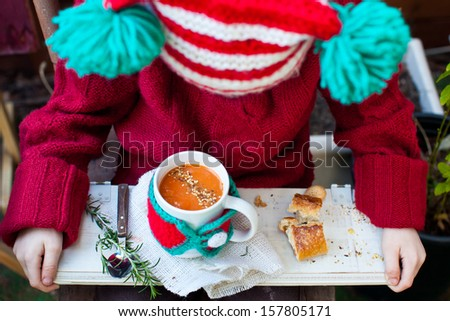 Kid in Christmas Hat holding a Mug of Tomato Soup with Seeds. Also available in vertical format.  - stock photo