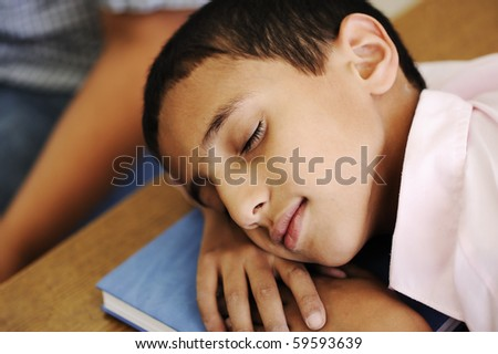 Kid in classroom on desk falling asleep on his notebook - stock photo