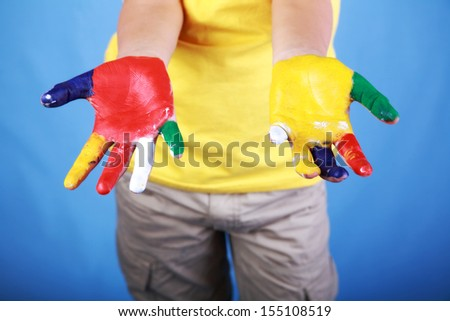 Kid in colorful t-shirt showing his hands painted with multicolored paints as an education concept  - stock photo