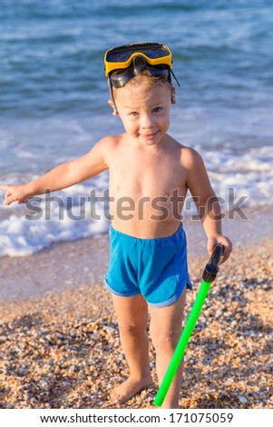 Kid in diving mask invites the sea - stock photo