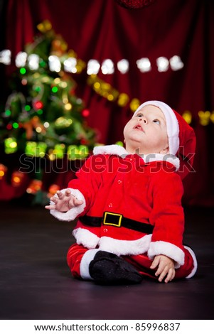 Kid in Santa costume looking up - stock photo