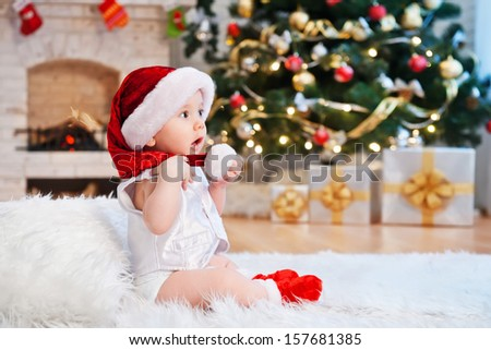 Kid in Santa hat, in a holiday room - stock photo