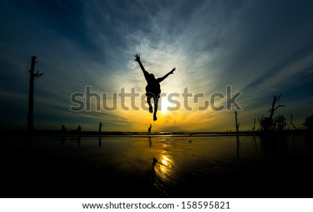 Kid in silhouette jumps at beach during sunset - stock photo
