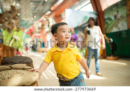 Kid in the museum. Look at something. Smart asian kid smiling, was listening teachers - stock photo