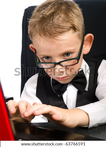 Kid in white shirt and bow tie types on laptop - stock photo